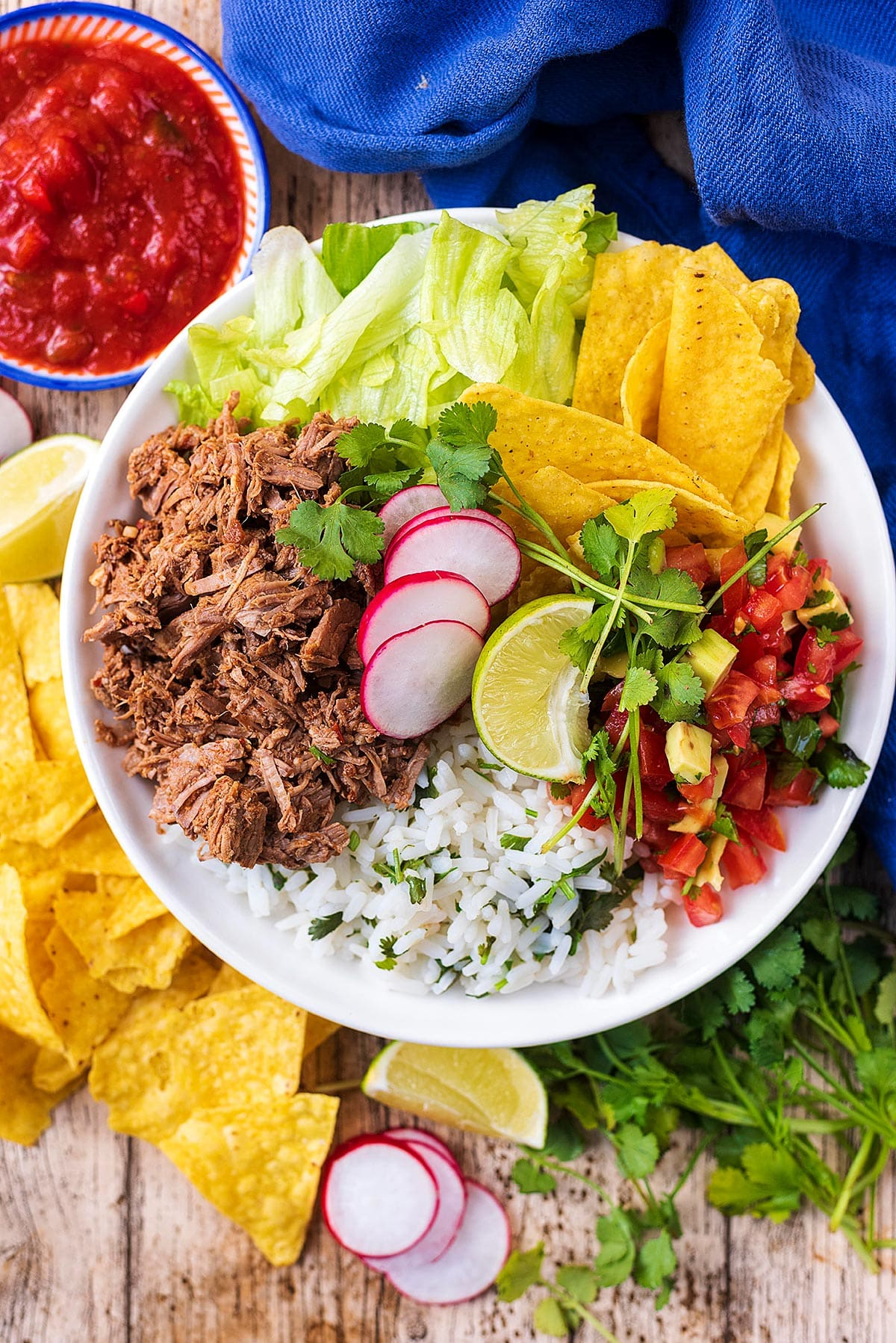 A burrito bowl consisting of shredded beef, lettuce, salsa, rice, tortilla chips and sliced radish