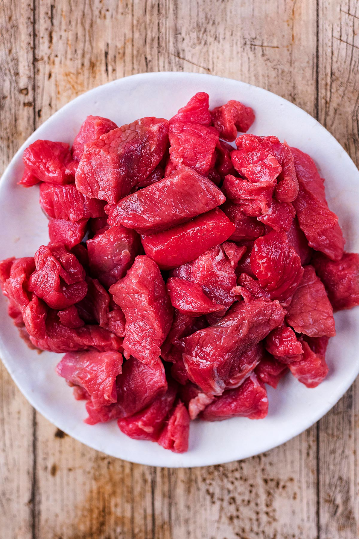 A plate of raw beef cubes