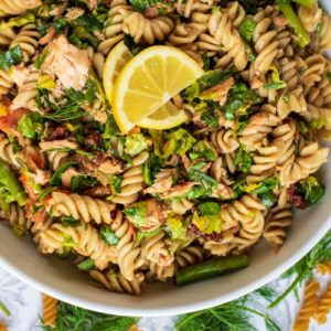 Salmon Pasta Salad in a white dish with lemon slices on top