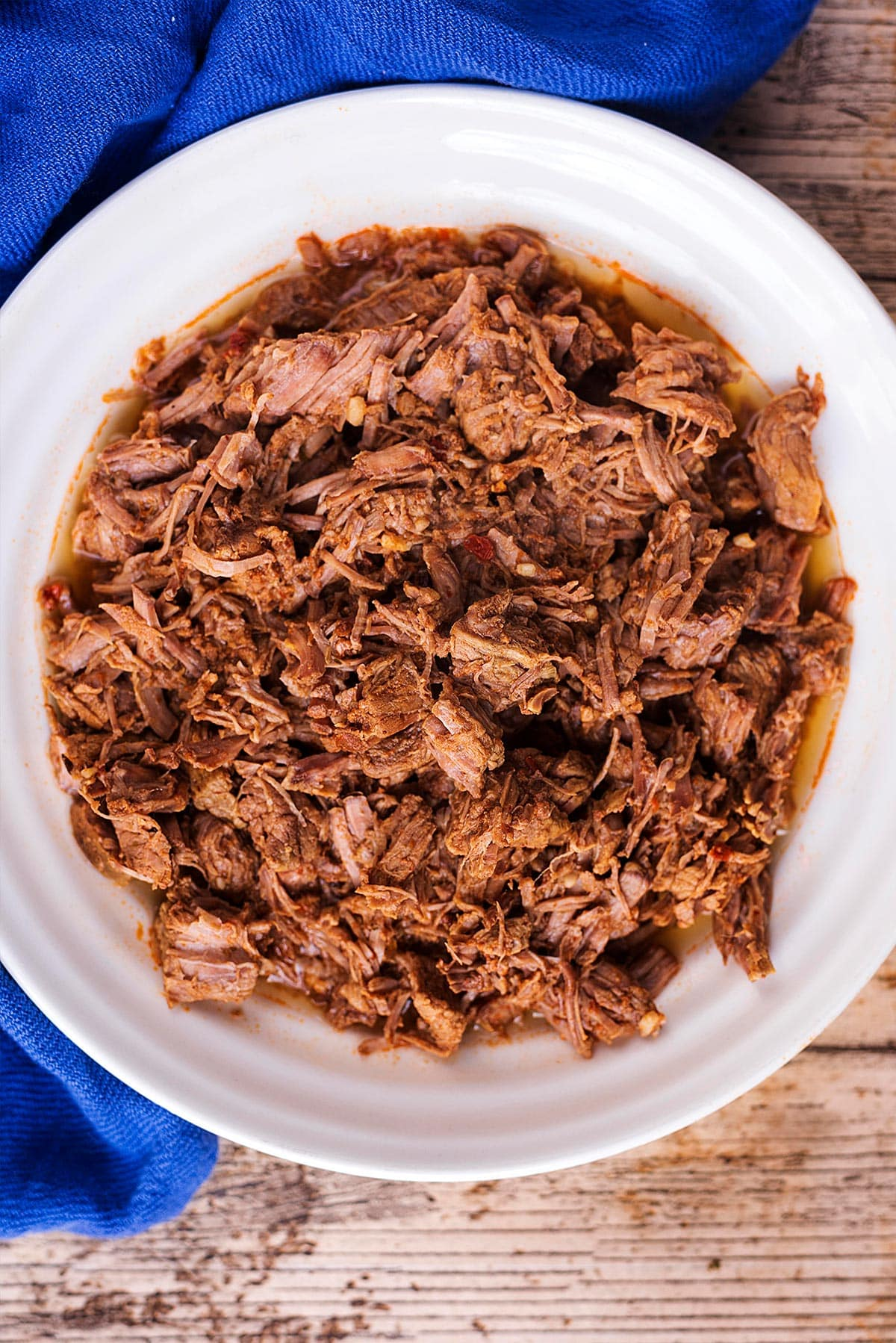 A bowl of pulled beef next to a blue towel