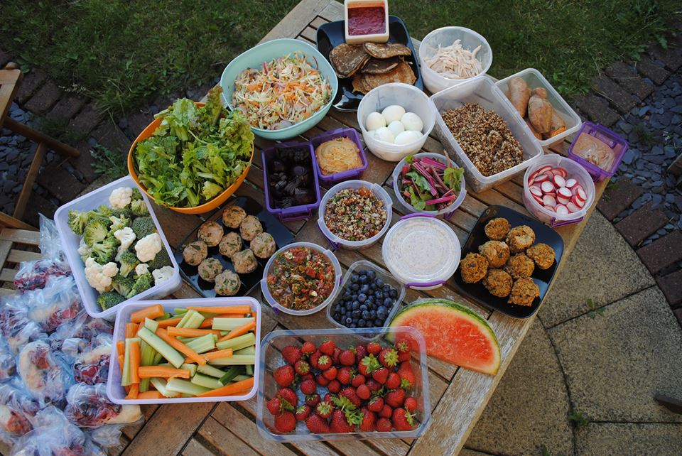 A wooden table covered in prepared food in bowls, plastic containers, bags or on plates