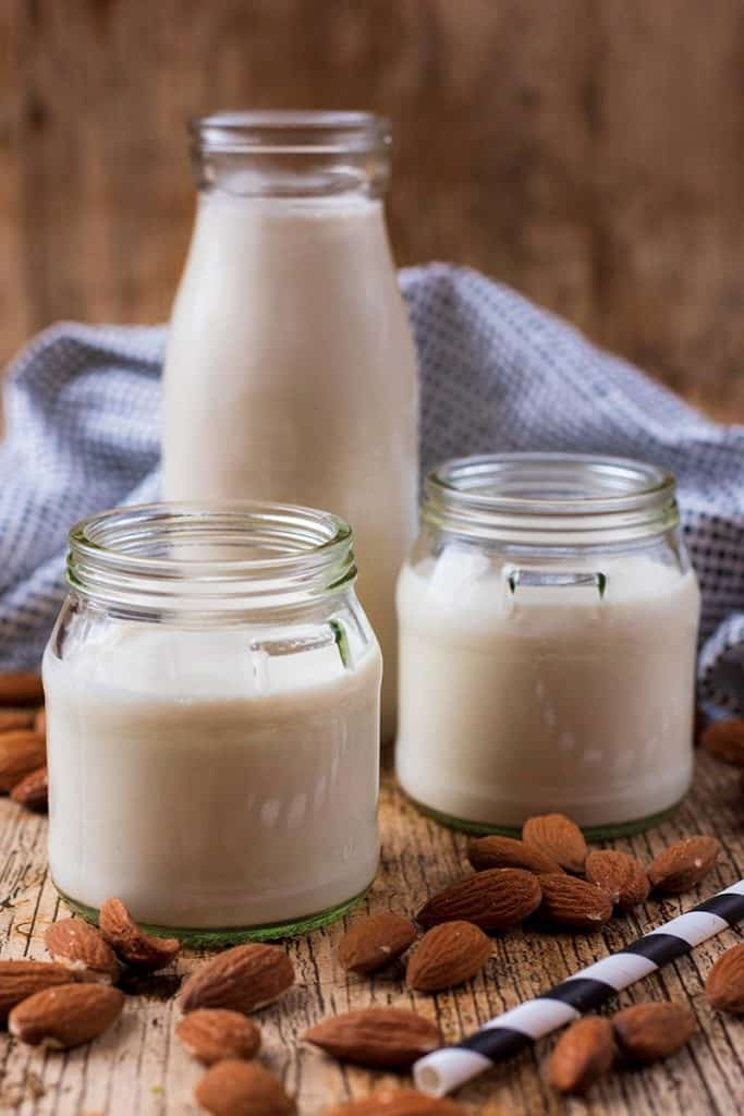 Homemade almond milk in a milk bottel and two small glass jars. Almonds are scattered around the surface