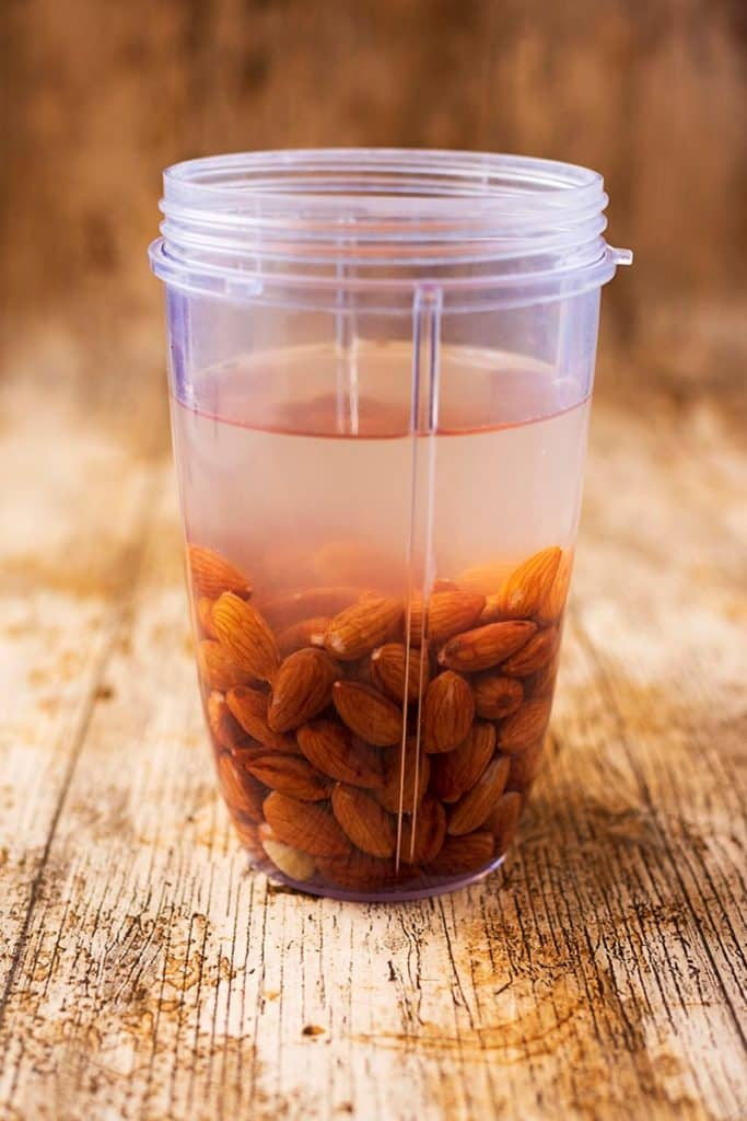 Almonds and water in a blender jug