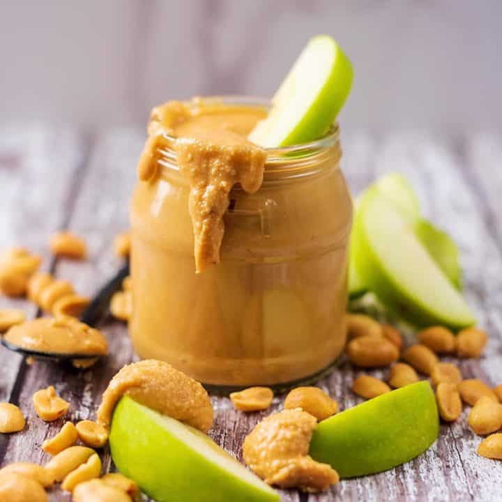 A jar of homemade peanut butter with slices of apple and peanuts