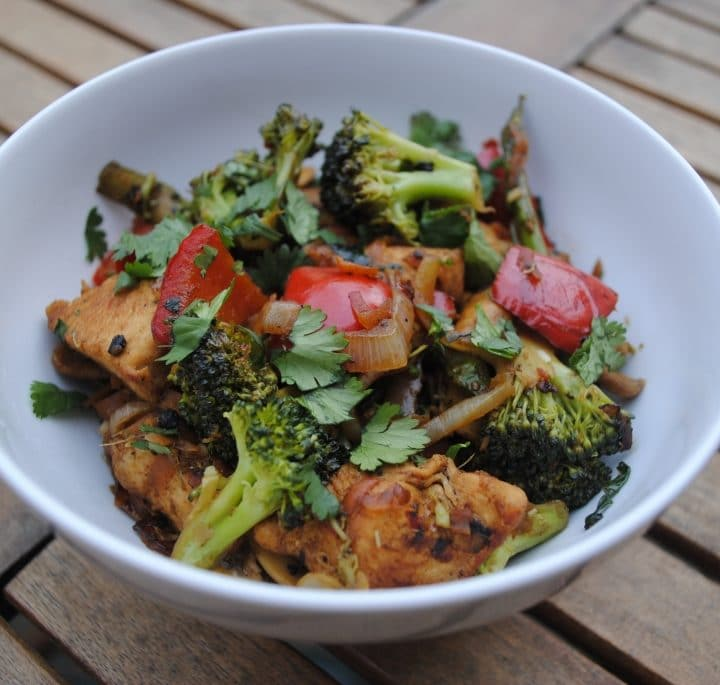 Chicken stir fry in a white bowl on a wooden table