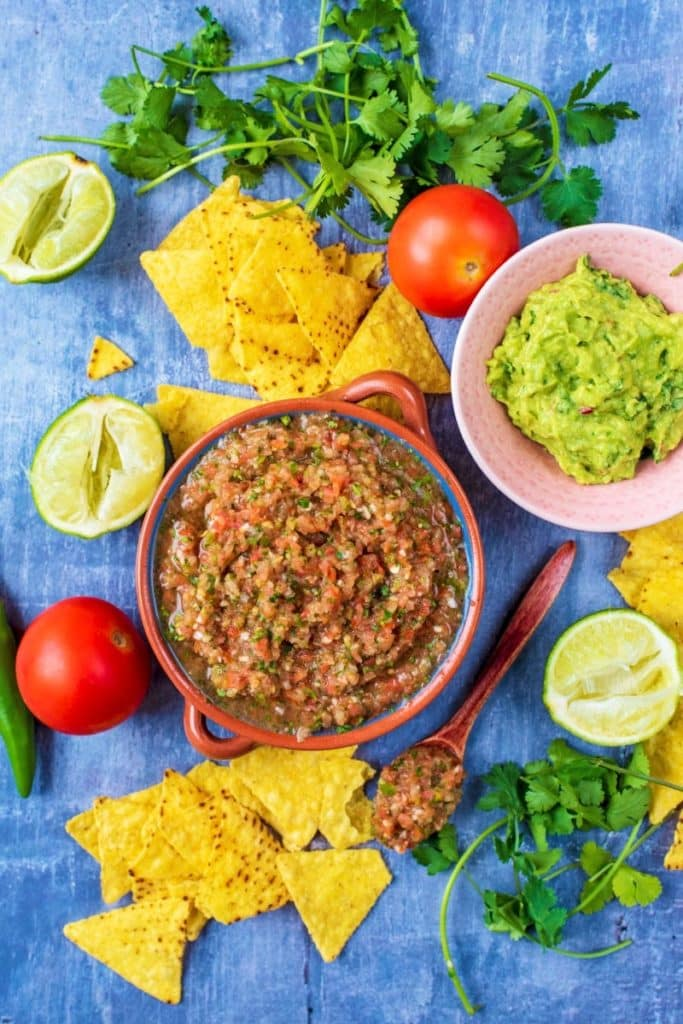 A bowl of Salsa Picante surrounded by tortilla chips, guacamole, limes and herbs