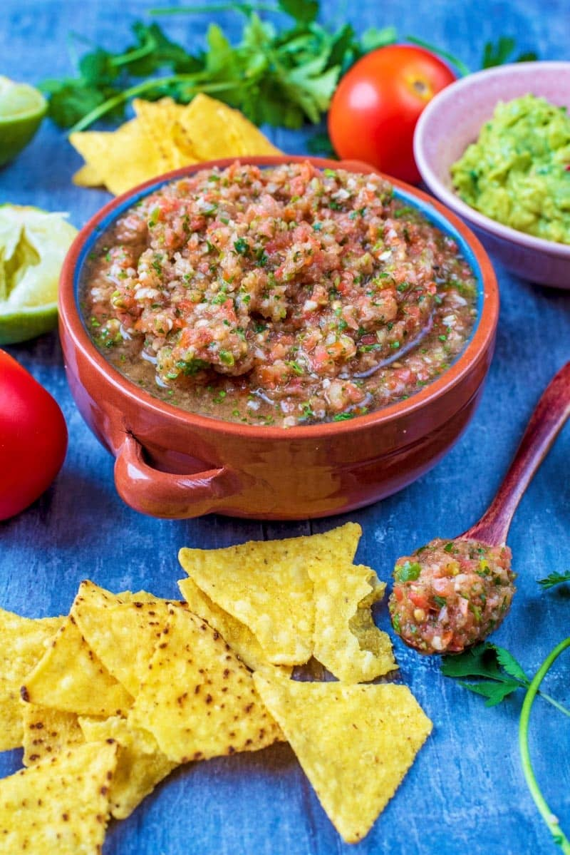 A bowl of salsa with scattered tortilla chips