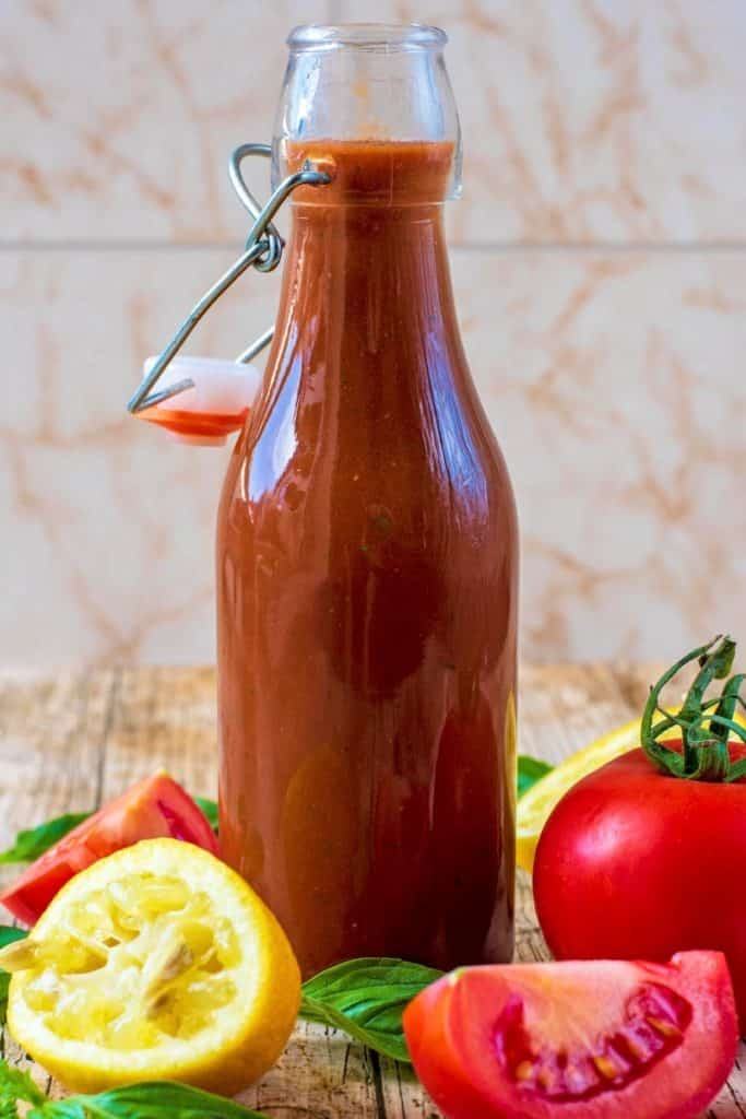 Tomato Vinaigrette in a glass bottle in front of a tiled background
