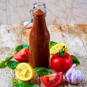 Tomato Vinaigrette surrounded by tomatoes, lemons garlic and basil