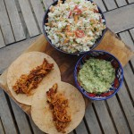 Pulled Chicken Tacos on a serving board with slaw and guacamole