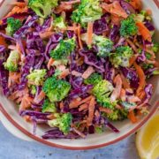 Broccoli Slaw in awhite serving dish next to lemon wedges