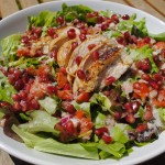 Pomegranate dressing on sliced chicken and salad