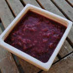 Strawberry Puree in a square white bowl sat on a wooden table