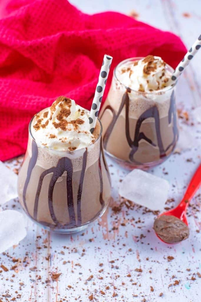 Two Mocha Frappuccinos with an ice cube and spoon