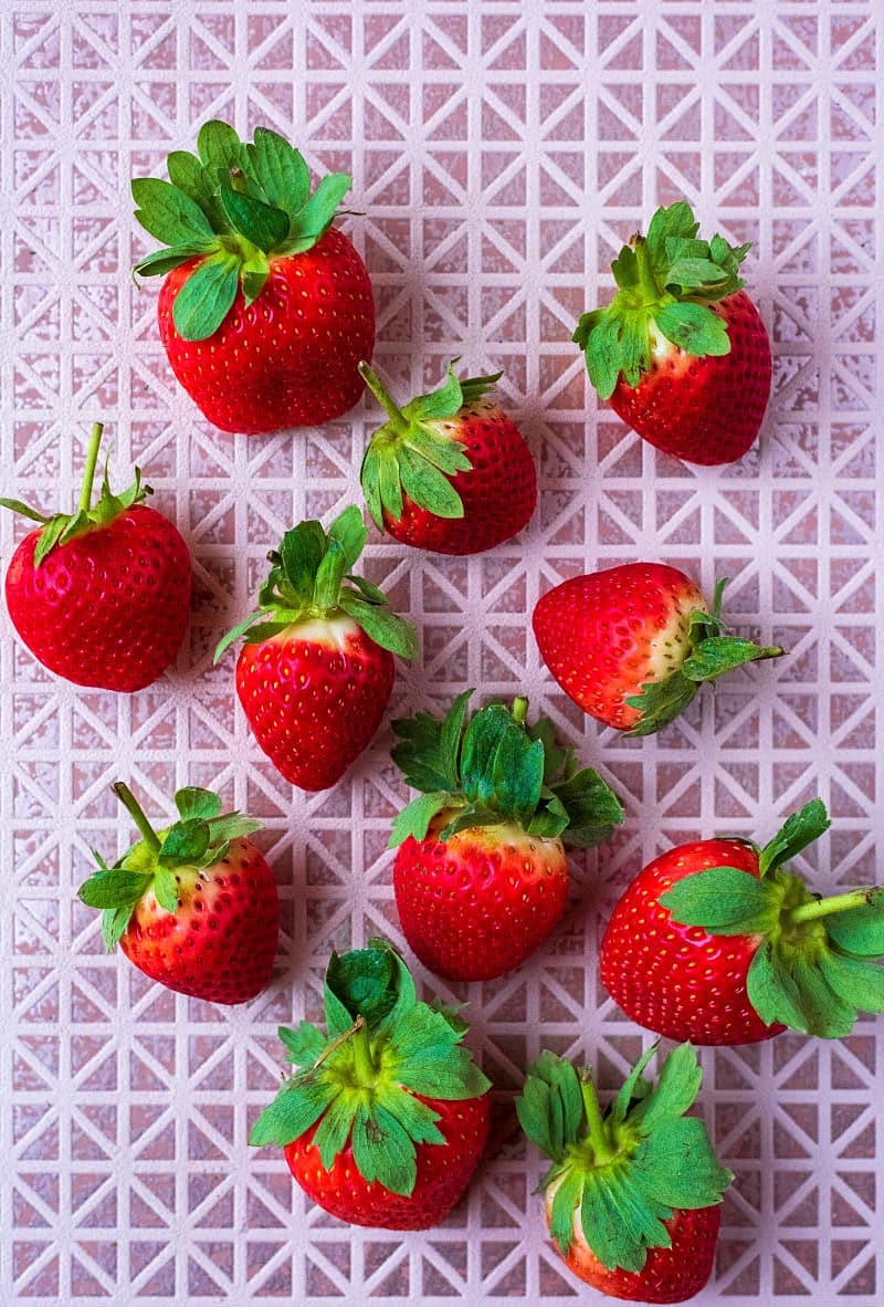 Eleven fresh strawberries on a tiled surface