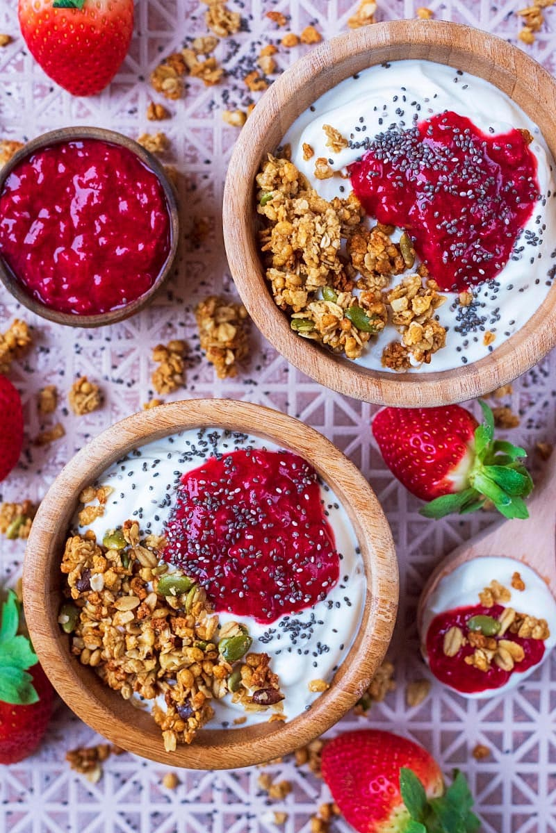 To bowls of yoghurt and granola with strawberry puree on top. Fresh strawberries surround the bowls