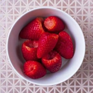 A small bowl of hulled strawberries