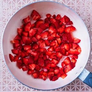 A saucepan with small chunks of strawberry in it