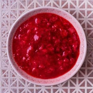A small pink bowl full of strawberry puree