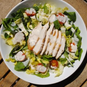 Chicken Caesar Salad in a large white bowl on a wooden table