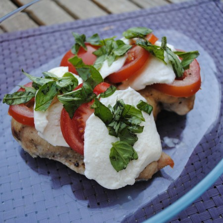 Caprese chicken on a glass plate topped with herbs