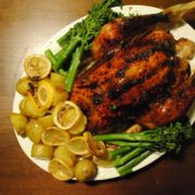 Honey Soy Chicken with potatoes, asparagus and lemon slices all on a large white plate