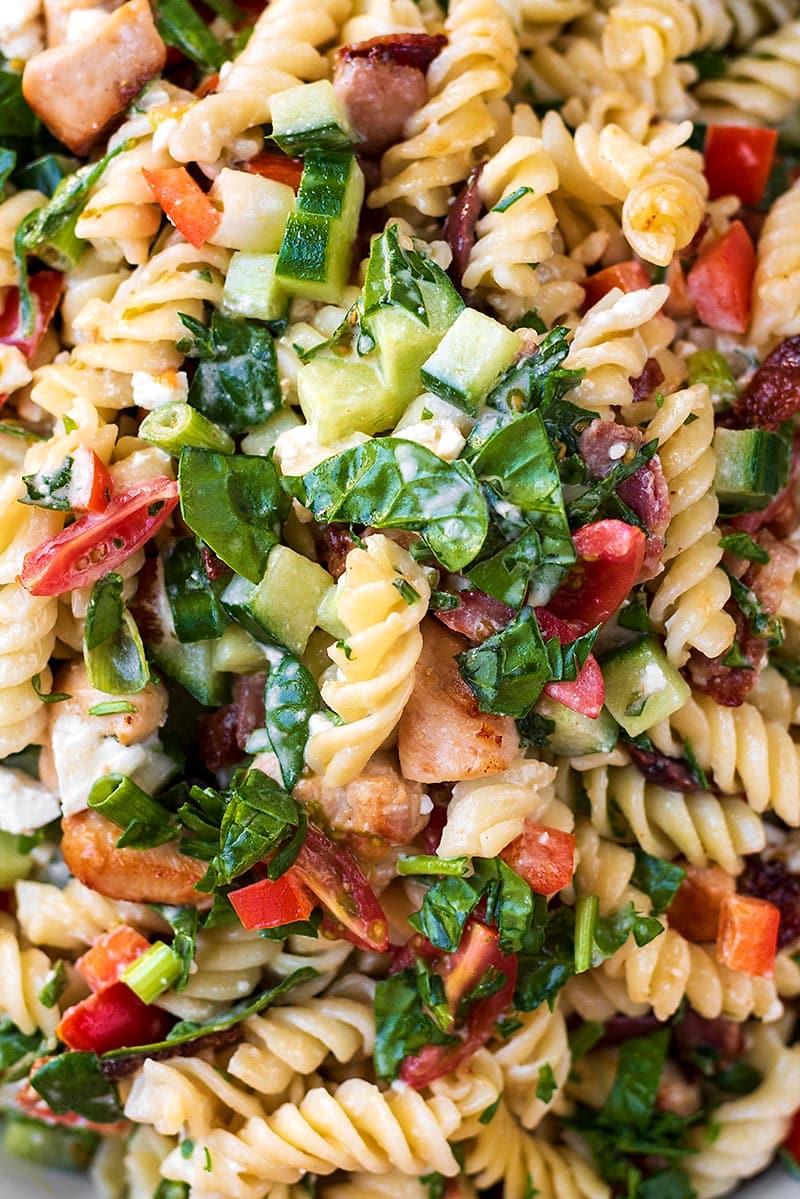 Cooked pasta mixed with chopped salad vegetables and a creamy sauce