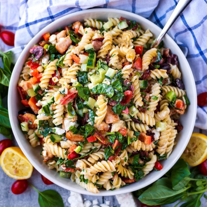 Chicken Pasta Salad in a large round bowl surrounded by lemon, cheese and basil leaves
