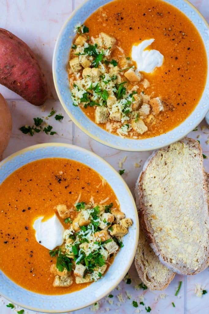 Two bowls of Sweet Potato and Butternut Squash Soup next to some buttered bread