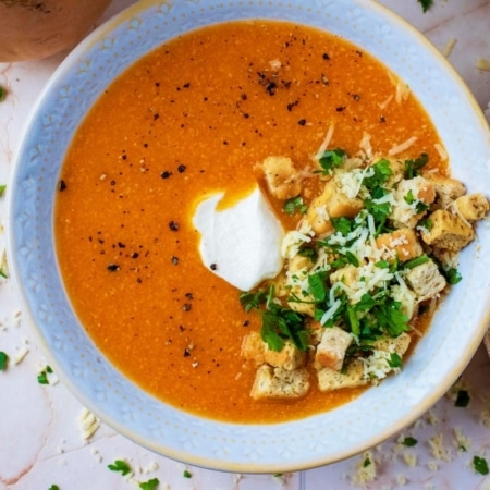 Sweet Potato and Butternut Squash Soup in a bowl topped with croutons, herbs and a dollop of cream