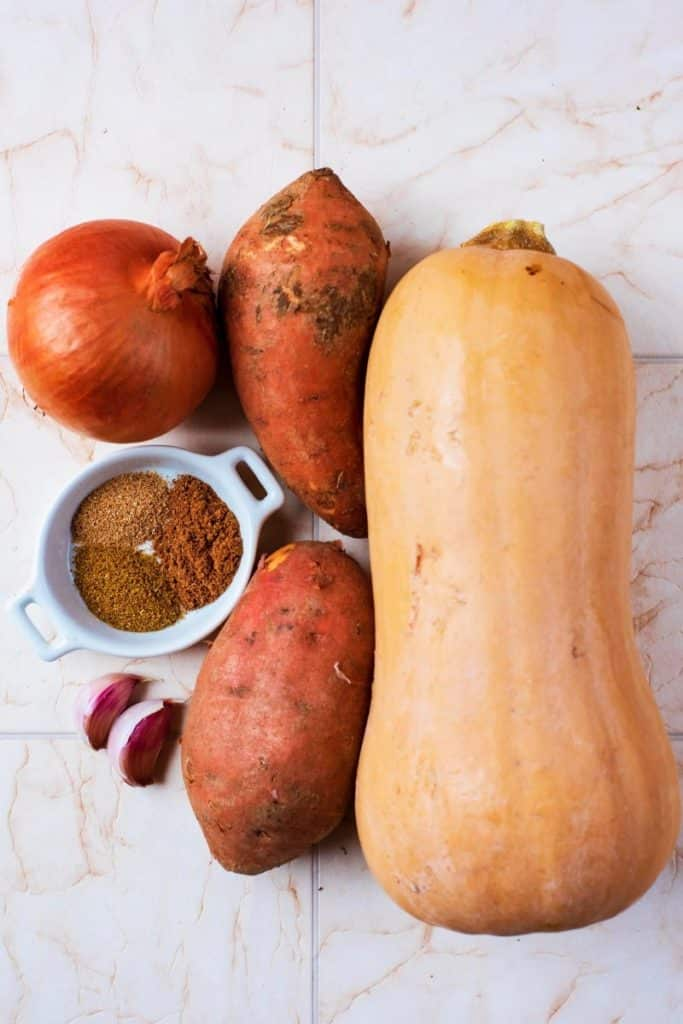A butternut squash, two sweet potatoes, an onion, garlic and spices on a tiled surface