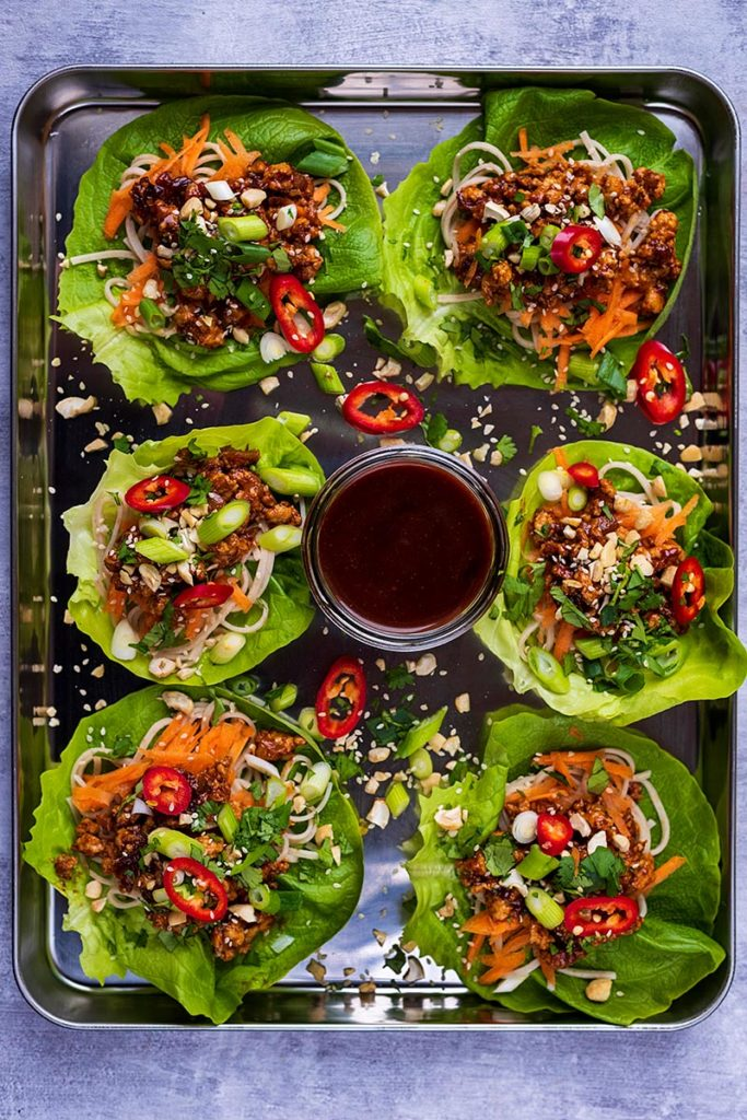 A large metal tray with six chicken lettuce wraps and a bowl of sauce