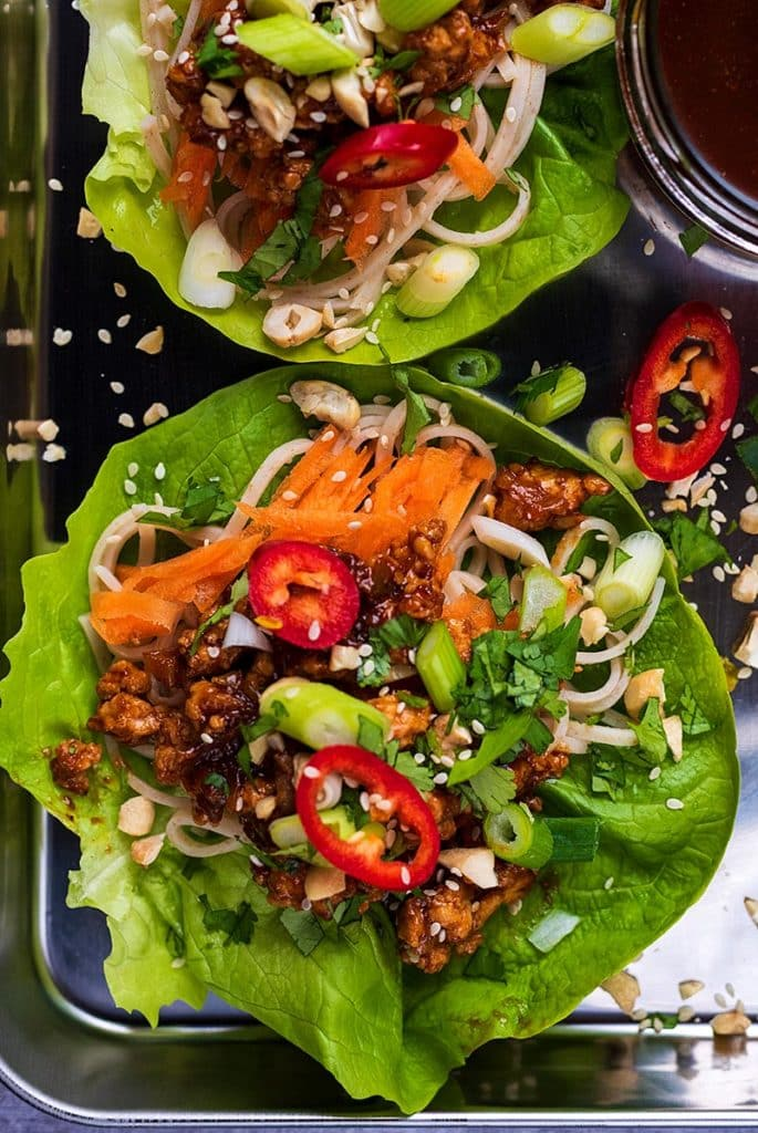 A large lettuce leaf topped with ground chicken, vegetables and sesame seeds