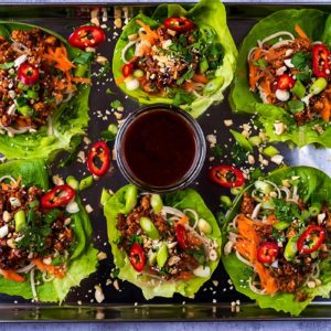 Six Asian Lettuce Wraps on a serving tray with a pot of hoisin sauce