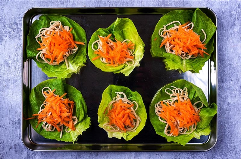 Six lettuce leaves topped with cooked noodles and grated carrot