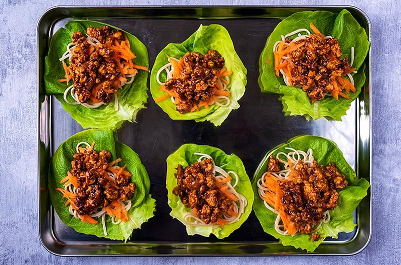 Six lettuce leaves topped with cooked noodles, carrot and ground chicken