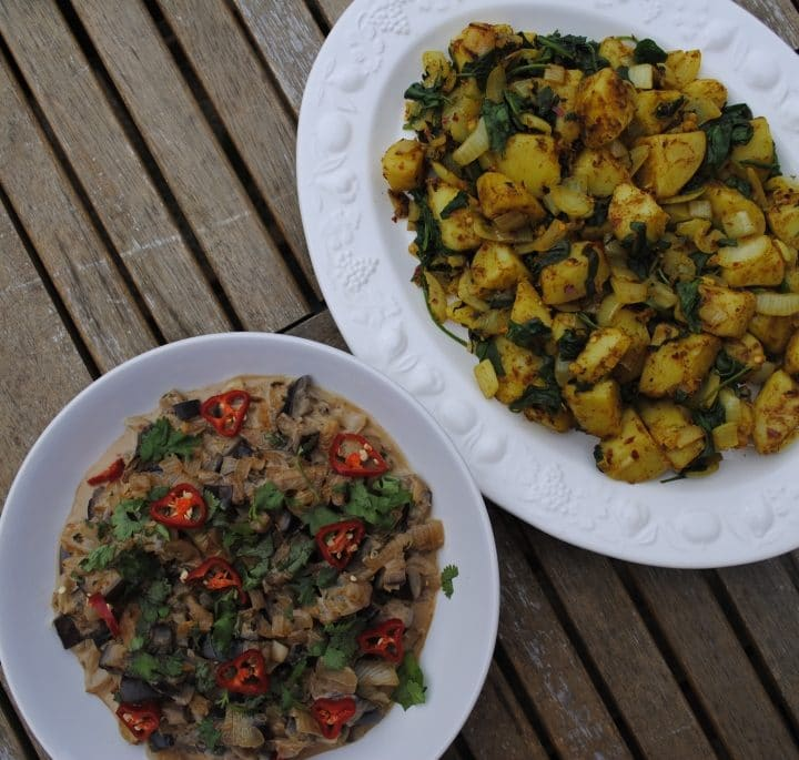 Aubergine curry in a bowl next to a plate of sag aloo