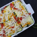 Roasted Vegetable Lasagne in a baking dish next to some basil leaves