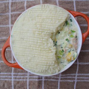 Healthy Fish Pie in an orange dish on a brown towel