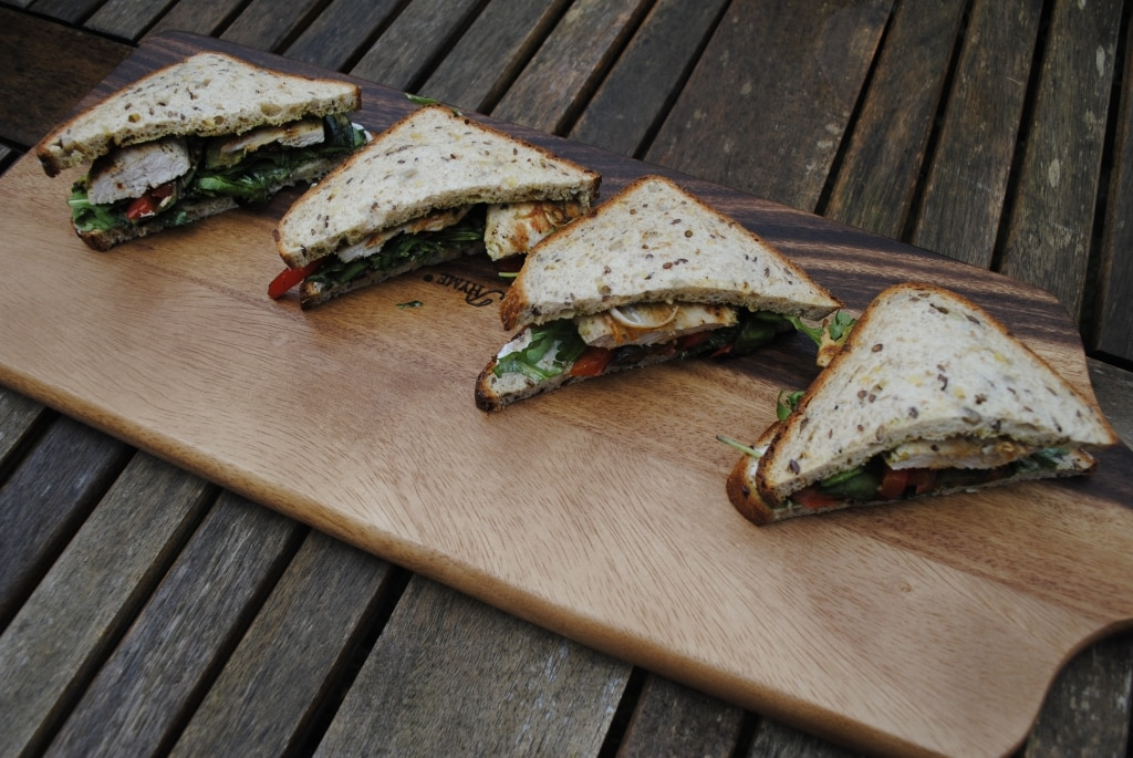 Pesto Chicken Sandwich halves on a wooden serving board