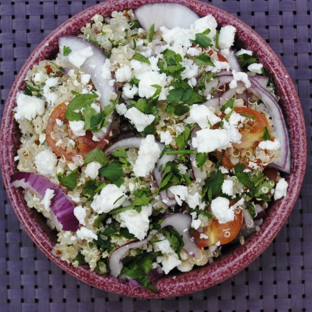 Quinoa Greek Salad in a shallow bowl on a purple mat