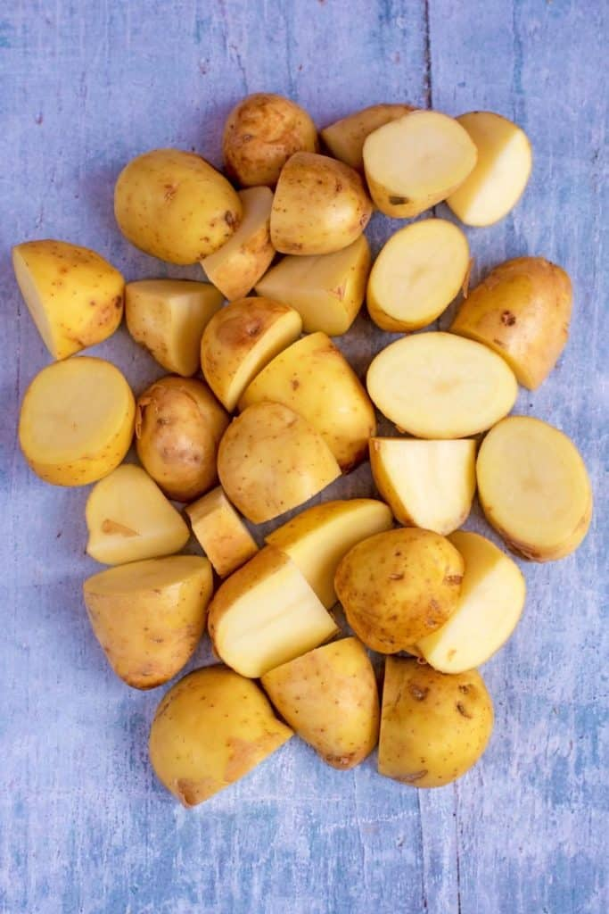 A pile of cut potatoes on a blue background
