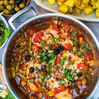 Italian Chicken in a large silver pan surrounded by roasted potatoes, salad, bread and olives