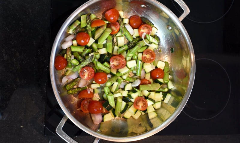 Chopped vegetables cooking in a large silver pan