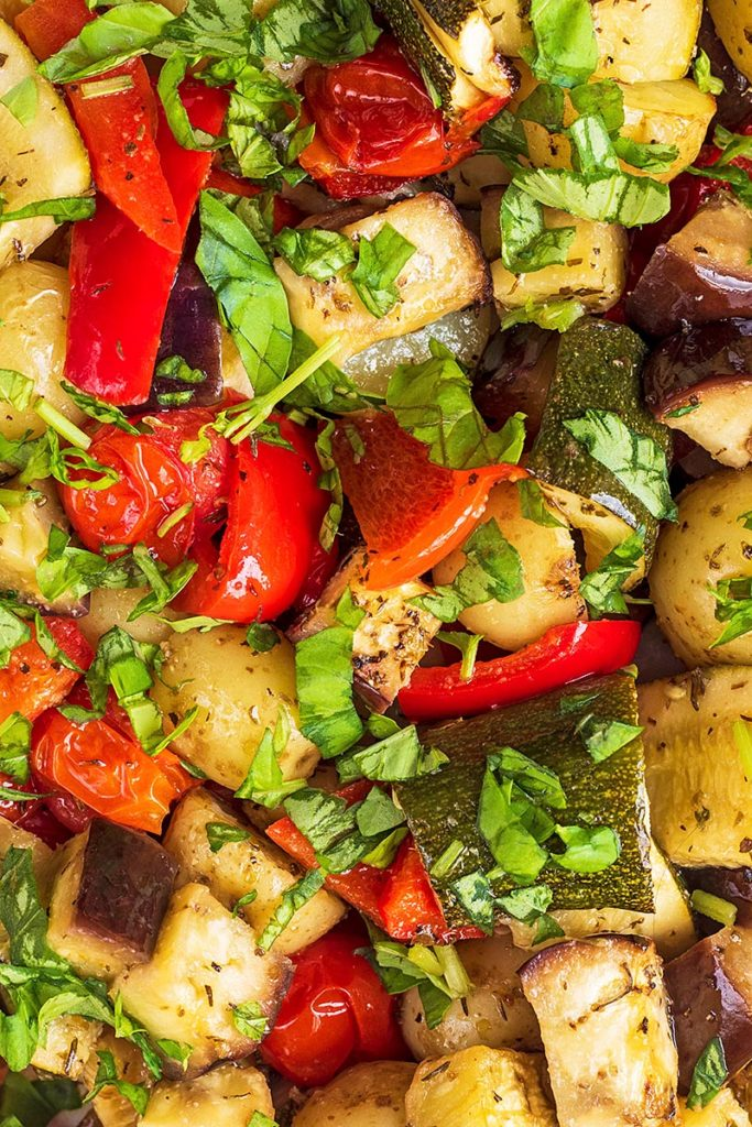 Chunks of potatoes, bell pepper, courgette and aubergine covered in chopped herbs