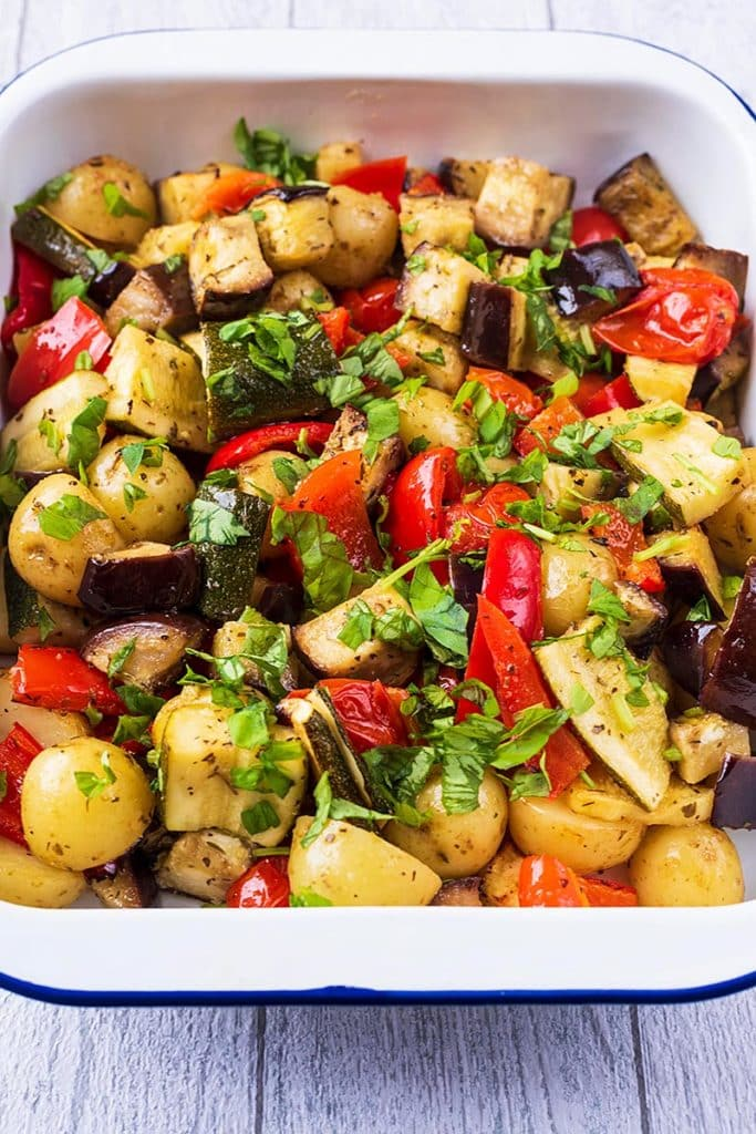 Chunks of roasted vegetables in a white oven dish