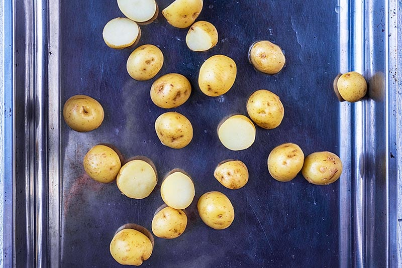 Baby potatoes, cut in half, in a roasting tin