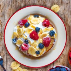 A plate of Banana Pancakes topped with cream and berries