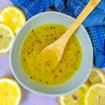 Lemon vinaigrette in a bowl with a small wooden spoon.