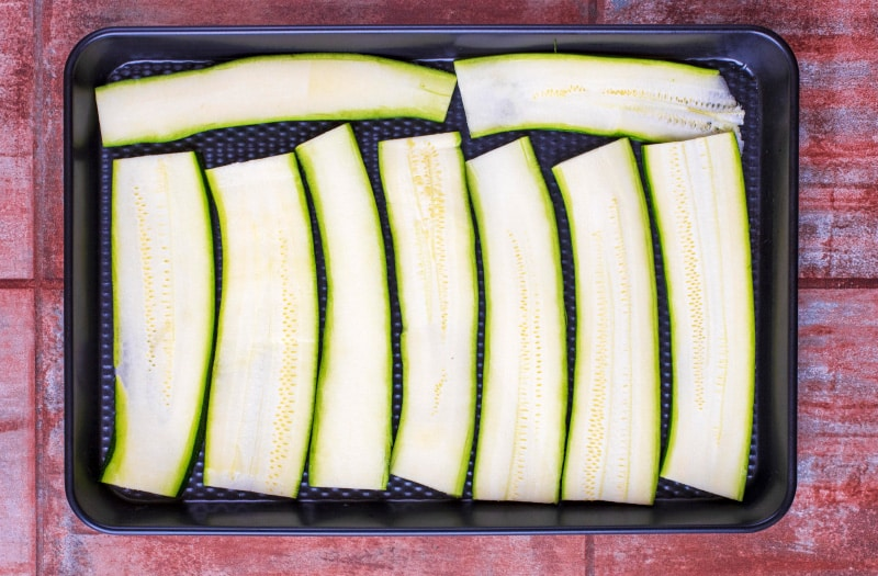 Strips of zucchini laid out on a black baking tray